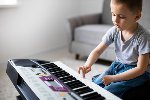 Little boy learning how to play the piano