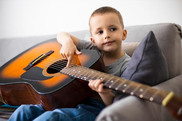 기타를 연주하는 방법을 배우는 어린 소년