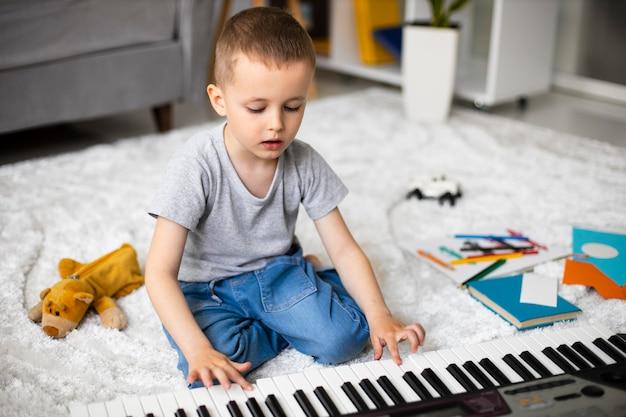 피아노를 연주하는 방법을 배우는 어린 소년