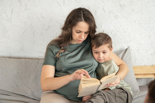 Little boy learning to read a book mom helps him happy family sitting at the bed  boy reading a book spending time together concept