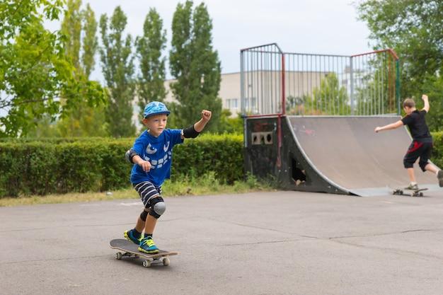 スケートパークで彼のボード上で彼のバランスとスタンスを練習するスケートボードを学ぶ小さな男の子