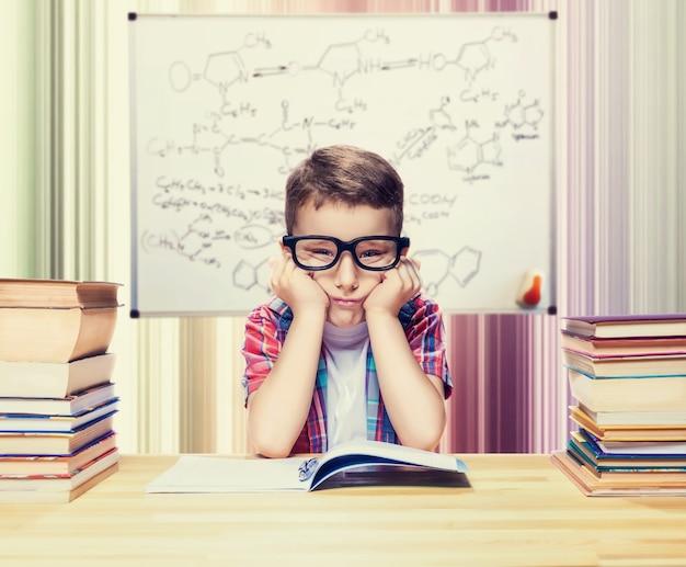 Маленький мальчик учится уроки в школьной библиотеке. ученик в очках против книжных полок