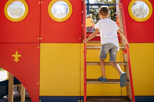 小さな男の子は遊び場でのんびり、幸せな子供時代。子供はトランポリンで遊ぶ