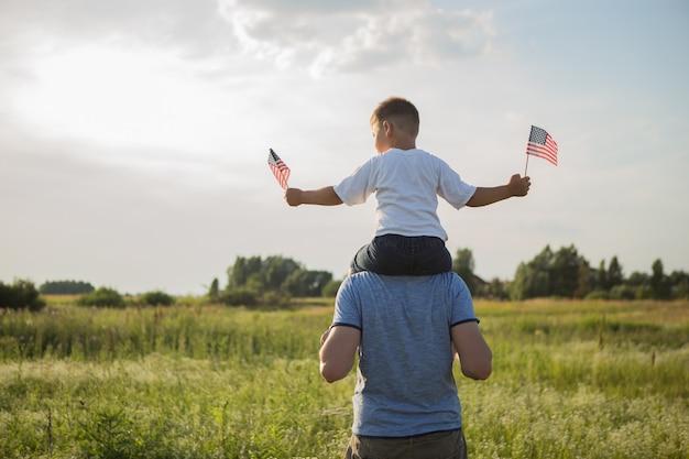 어린 소년은 녹색 필드에서 바람에 미국 국기를 손에 날리게합니다.