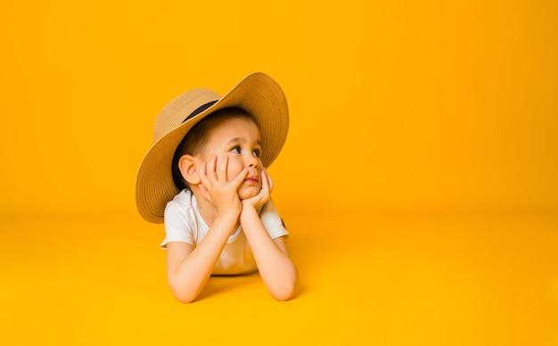 小さな男の子は、テキストの場所がある黄色い表面の麦わら帽子に横たわっています