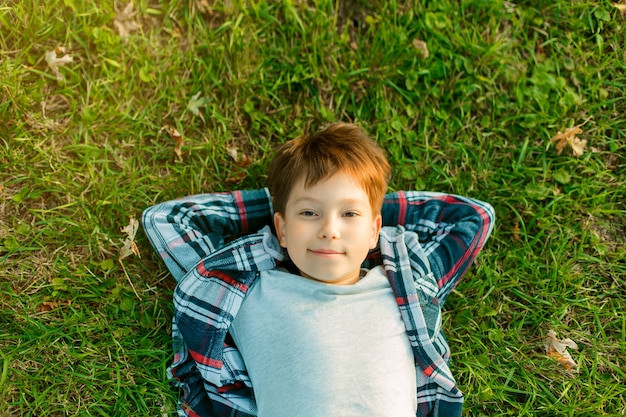 Маленький мальчик лежит на зеленой траве