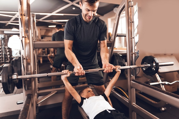 Little boy lifts the barbell and his father helps him.