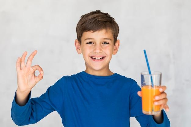 Little boy liking his orange juice