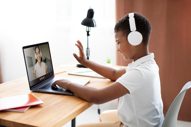 Little boy listening to his teacher through headphones