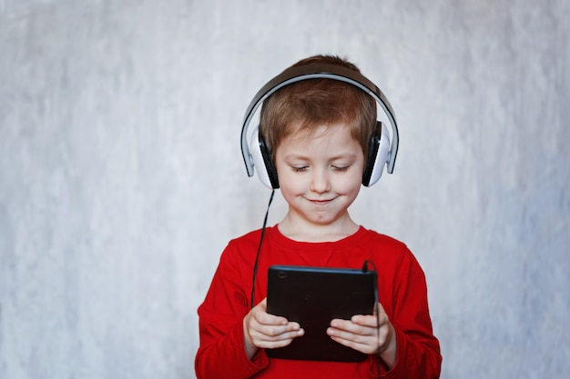 Little boy listening to music from his tablet on his headphones