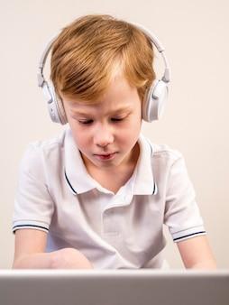 Little boy listening to music through headphones