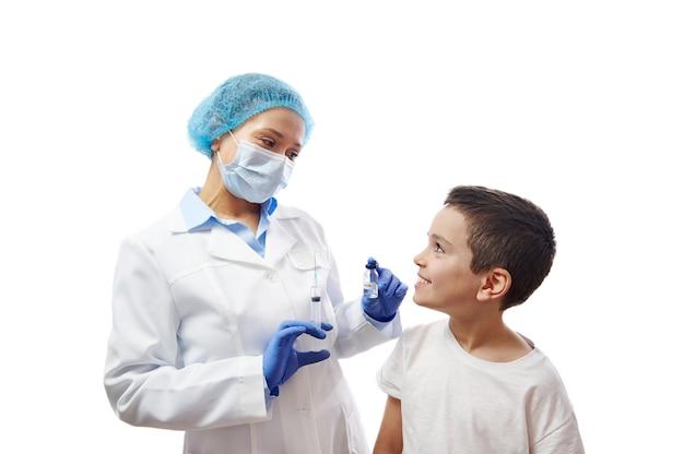 手にワクチンバイアルと注射器を備えた医療マスクで笑顔の医者を見ている少年