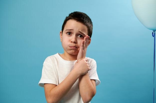 어린 소년 정면을보고 그의 손으로 그의 뺨을 덮고 정면에 치통을 표현