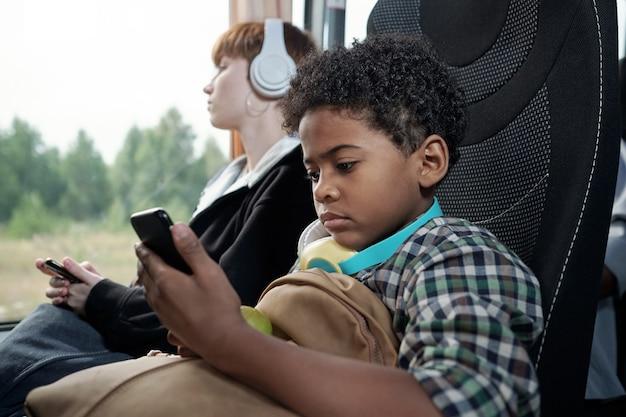 Маленький мальчик, глядя на экран смартфона в автобусе