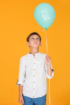 Little boy looking at a blue balloon
