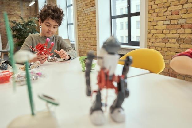 테이블에 앉아 세부 사항으로 가득 찬 기술 장난감을 확인하는 동안 바쁜 찾고 어린 소년