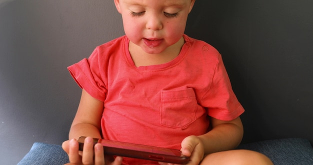Little boy looking enthusiastically screen phone sitting sofa