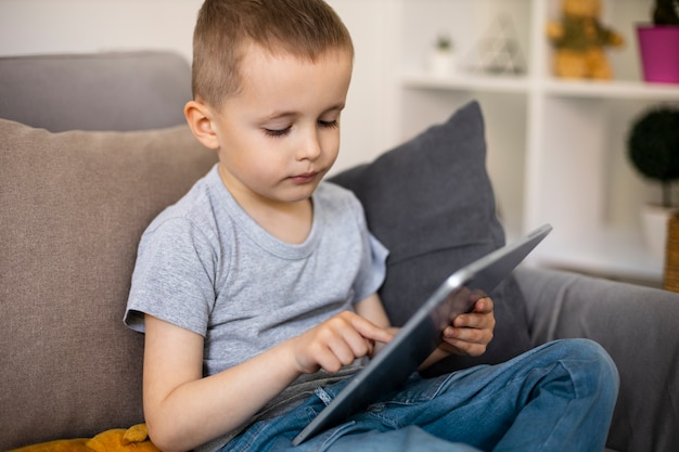Little boy looking at his tablet