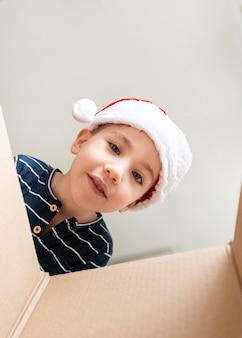 Маленький мальчик смотрит в подарочную коробку