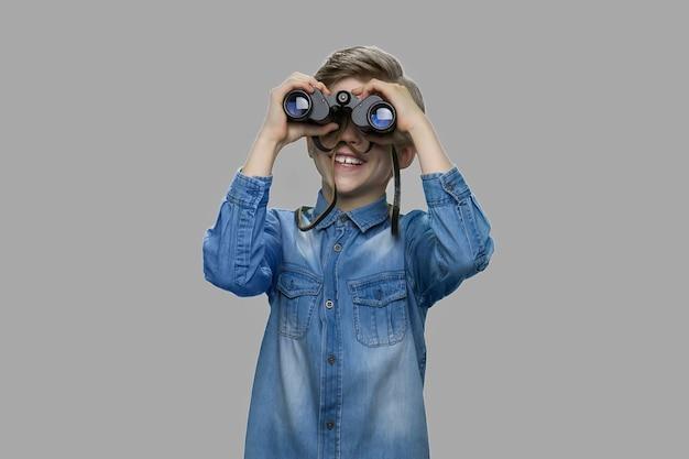 쌍안경을 통해 찾고 어린 소년입니다. 회색 배경에 쌍안경을 사용하는 데님 재킷에 호기심 많은 아이. 위치를 관찰하는 아이.