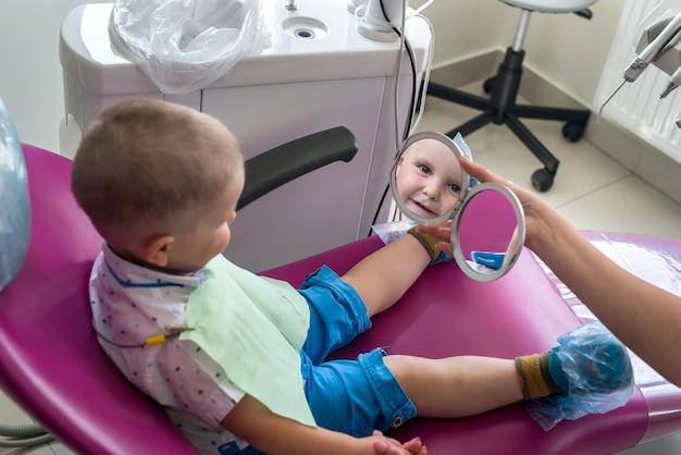 小さな男の子は、歯科用アームチェアに座っている鏡に映った自分の姿を見ています