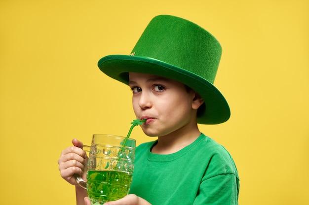 어린 소년은 성 패트릭의 날을 축하하는 클로버 잎 장식으로 빨대에서 녹색 음료를 마시면서 카메라를 바라 봅니다.