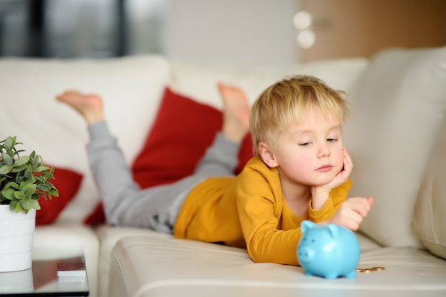 Little boy looks on moneybox and plans of what he can buy.