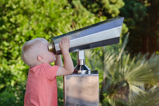 Little boy looks through binoculars for tourists at viewpoint on park