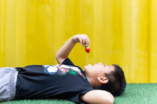 Little boy lying down eating strawberry isolated in yellow background.