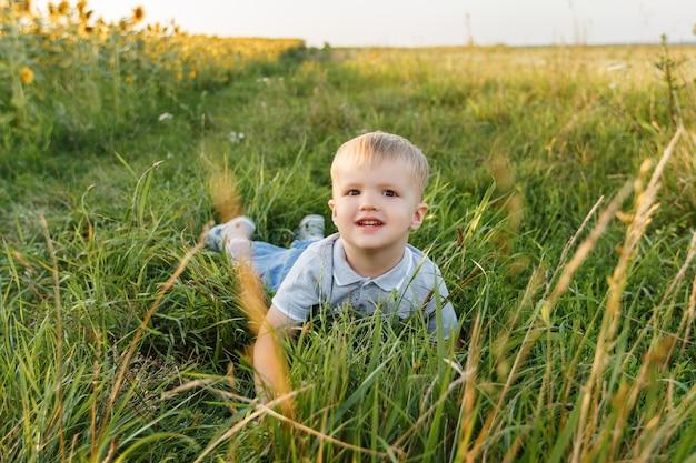 Маленький мальчик, лежащий на траве и улыбающийся трехлетний ребенок, развлекающийся в поле на закате