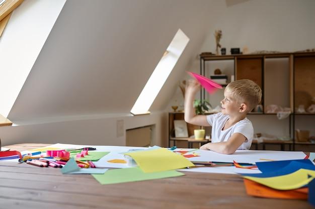 Маленький мальчик делает бумажный самолетик, ребенок в мастерской. урок творчества в художественной школе. молодой художник, приятное хобби, счастливое детство