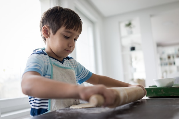 Little boy making dough for delicious sweet