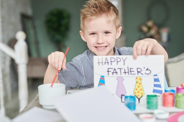 Маленький мальчик делает отцов день карты