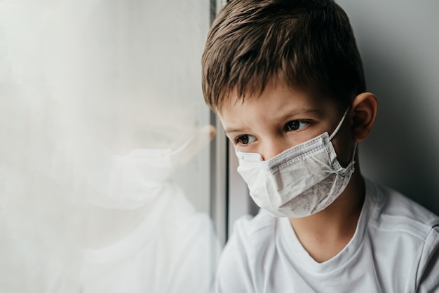 A little boy in a medical mask is sitting at home in quarantine because of coronavirus and covid -19 and looks out the window.