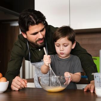 Little boy mixing eggs for dough