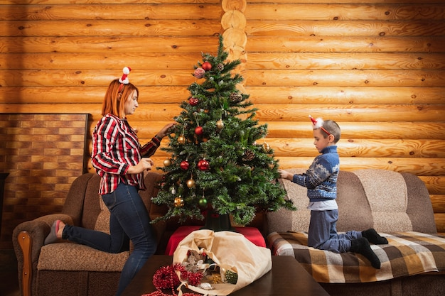 A little boy and mother decorates an artificial christmas tree with glass balls in a country house