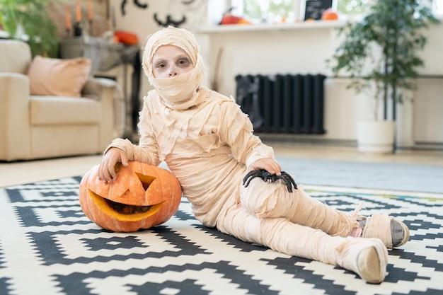 Little boy mummy with spider and jackolantern lying on the floor