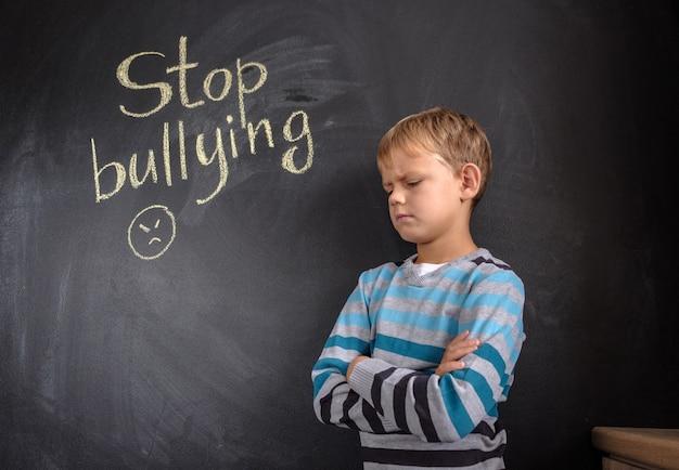 Little boy near chalkboard with words