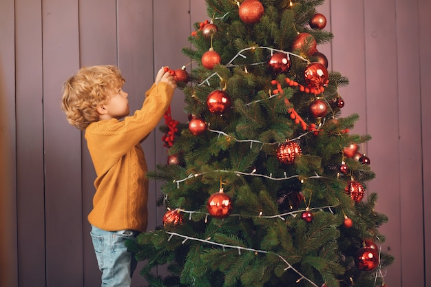 Little boy near christmas tree in a brown sweater