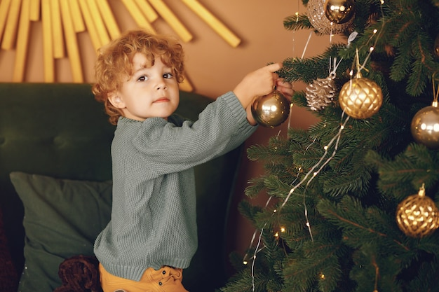 Little boy near christmas tree in a gray sweater