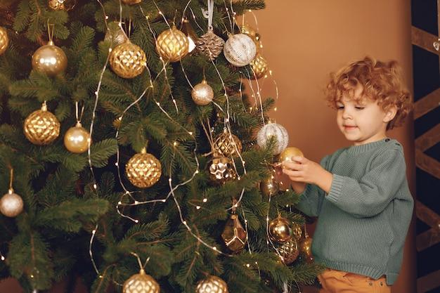 Маленький мальчик возле елки в сером свитере