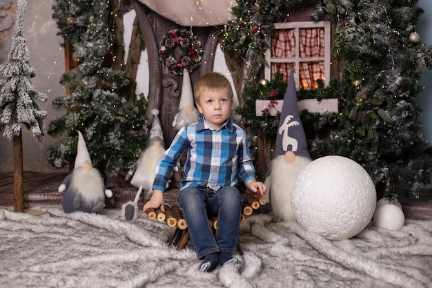 Маленький мальчик возле елки, игрушечного домика и гномов.