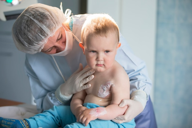 A little boy nurse treats a burn. a child in the hospital is injured. the doctor treats the baby. little hospital patient.