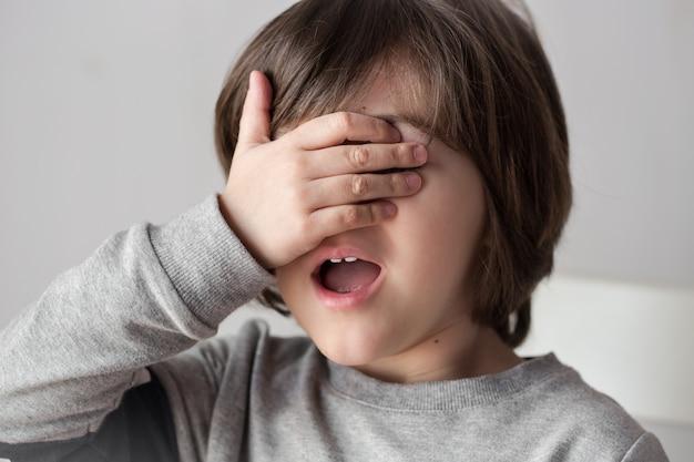 4歳の男の子が手で顔を覆った