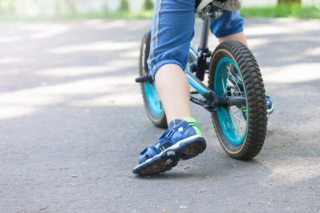 公園で夏に自転車の小さな男の子