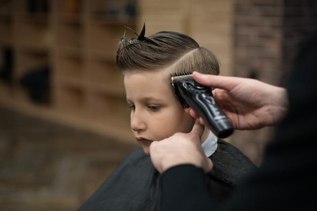 이발소에 머리에 어린 소년의 자에 앉는 다.