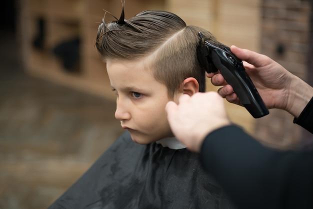 Маленький мальчик на стрижку в парикмахерской сидит на стуле.