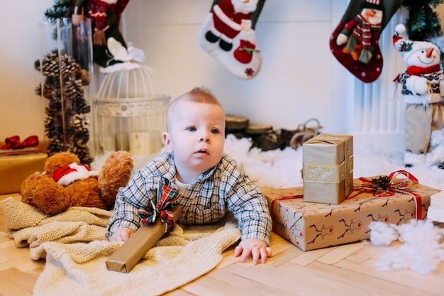 背景に暖炉とクリスマスの床に小さな男の子を提示します。クリスマス、新年、冬、休日の季節の概念。