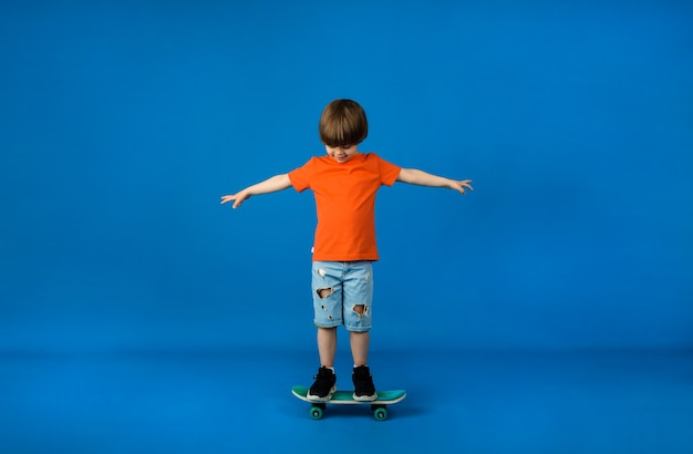 Little boy in an orange t-shirt and denim shorts rides a skateboard on a blue surface with space for text