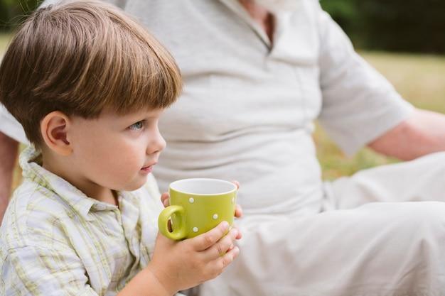 Little boy outdoor drinking tea